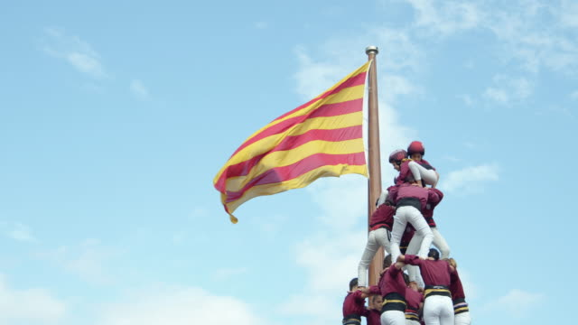 castellers human pyramid teamwork from catalonia. big catalan flag on the background - catalogna video stock e b–roll