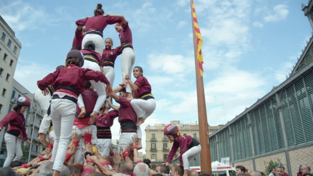 castellers human pyramid teamwork from catalonia. big catalan flag on the background - helmet stock videos & royalty-free footage