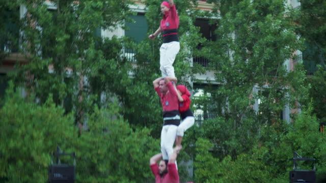 castellers kid climbing human pyramid teamwork from catalonia - human pyramid stock videos and b-roll footage