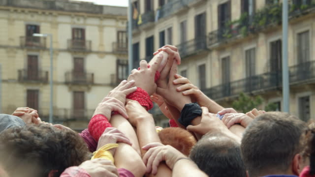 castellers touching hands, building human pyramid castle. catalonia barcelona old born district - human pyramid stock videos and b-roll footage