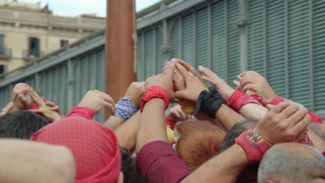 castellers touching hands preparing human castle. building the foundations. catalonia barcelona old born district - stability stock videos & royalty-free footage