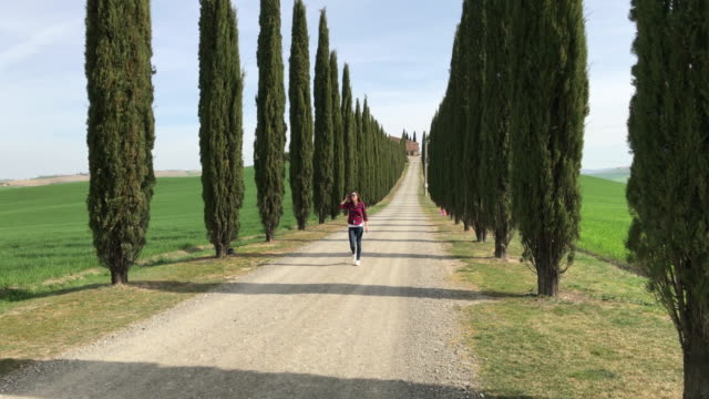 Castiglion d'Orcia, Orcia Valley, Siena, Tuscany. Girl in casual clothes is walking on a country road.