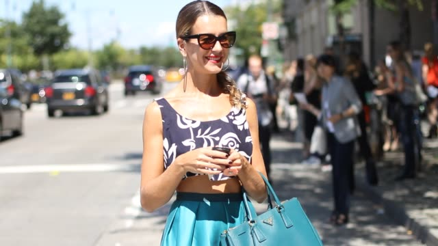 casting agent influencer and popular blogger natalie joos wears a floral crop top abstract teal skirt and prada bag a photographer takes a shot and... - teal stock videos & royalty-free footage