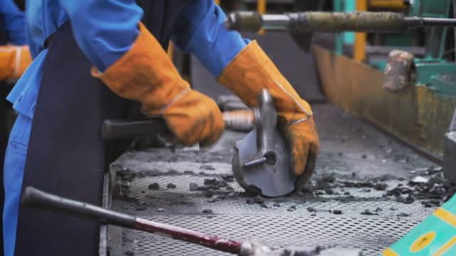 冷却ラインの鋳造部品、オペレータはハンマーでのゲージで良い部品を分離し、オペレータは鋳造工場で懸命に働く - お玉点の映像素材/bロール