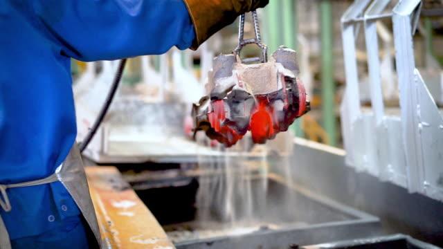 vídeos de stock, filmes e b-roll de peças de fundição em linha de resfriamento, operador tirar peças de fundição da caixa de transferência, operador trabalhar duro na fábrica de fundição - foundry