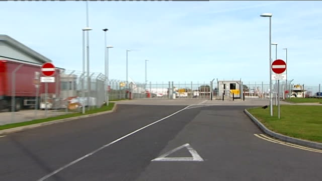 Castle Donington East Midlands Airport EXT Entrance road and security booth at airport ZOOM IN to airport taxiing beyond security fence Airport...