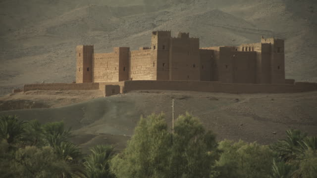 a castle like building stands at the foothills of the a mountain range, surrounded by harsh and dusty terrain. - religious illustration stock videos and b-roll footage
