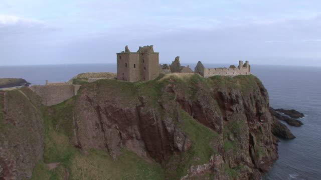 WS Castle on rocky headland surrounded by sea / Stonehaven, Scotland, United Kingdom