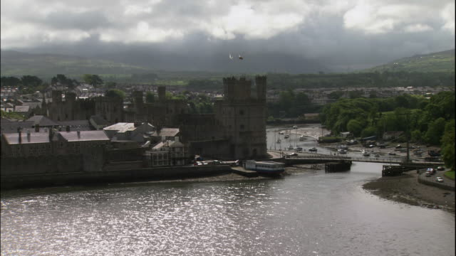 vidéos et rushes de a castle rises on the waterfront of caernarfon, wales. - pays de galles
