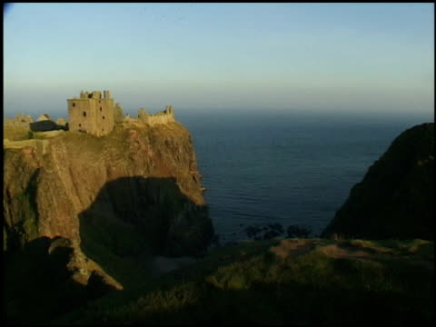 castle ruins stand on a cliff that overlooks the water. - aberdeen schottland stock-videos und b-roll-filmmaterial
