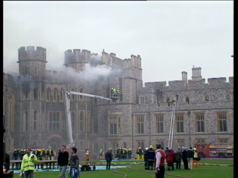 castle with smoke firemen on ground and firemen on crane being lifted up windsor castle fire 20 nov 92 - berkshire england stock videos & royalty-free footage