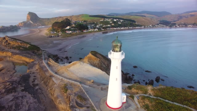 castlepoint lighthouse with castlepoint village in background. - new zealand stock videos & royalty-free footage