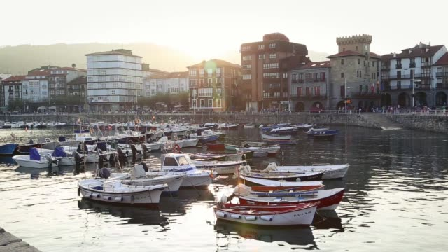 Castro Urdiales harbor with small fishing boats and the town hall behind.