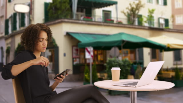 casual black woman using smartphone device at outdoor cafŽ.  portrait of woman sitting outside restaurant looking at cellphone handheld tech. - african american culture stock videos & royalty-free footage