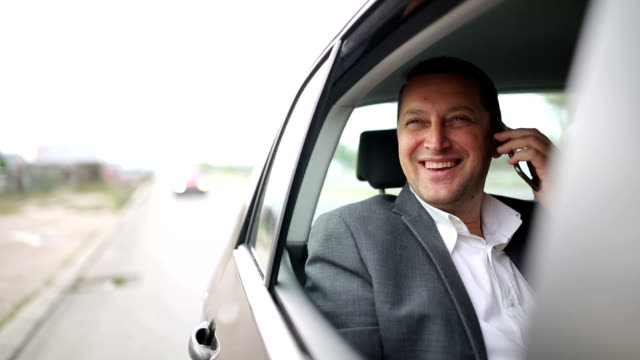 Casual business Mann auf Handy auf der Rückseite des Autos.
