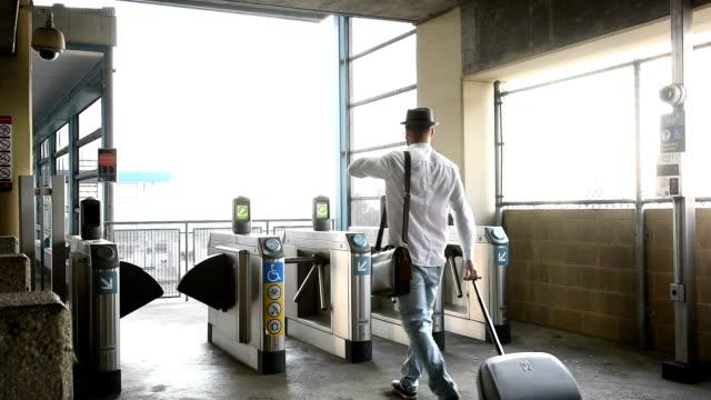 vídeos de stock, filmes e b-roll de homem de negócios casual rolando bagagem na estação de trem de metrô - bolsa tiracolo bolsa