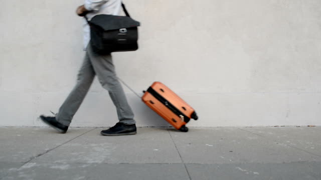casual businessman rolling luggage - profilo vista laterale video stock e b–roll
