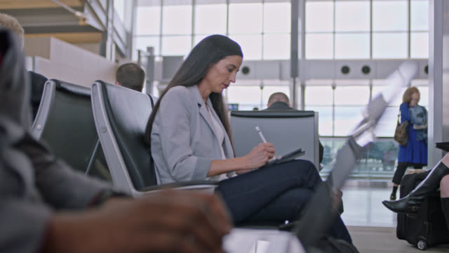 casual businesswoman works on tablet while waiting at airport terminal gate. - westernisation stock videos & royalty-free footage