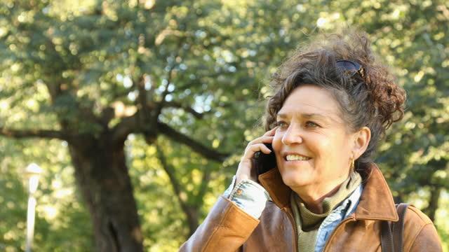 stockvideo's en b-roll-footage met toevallige rijpe vrouwen headshot die haar mobiele telefoon in openbaar park bij de tijd van de herfst met behulp van - alleen één oudere vrouw