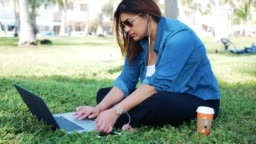 Casual millennial Latina using laptop in park in USA