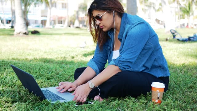 casual millennial latina using laptop in park in usa - body concern stock videos & royalty-free footage