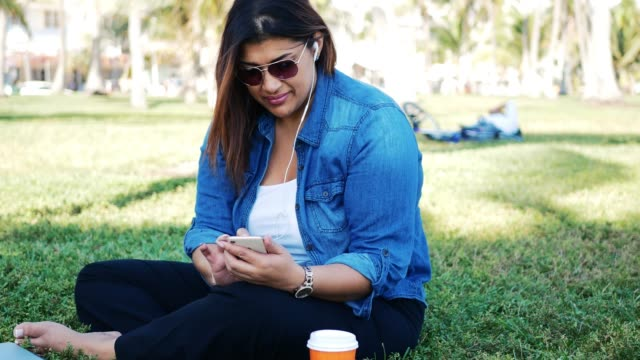 casual millennial latina using smart phone in park in usa - body concern stock videos & royalty-free footage