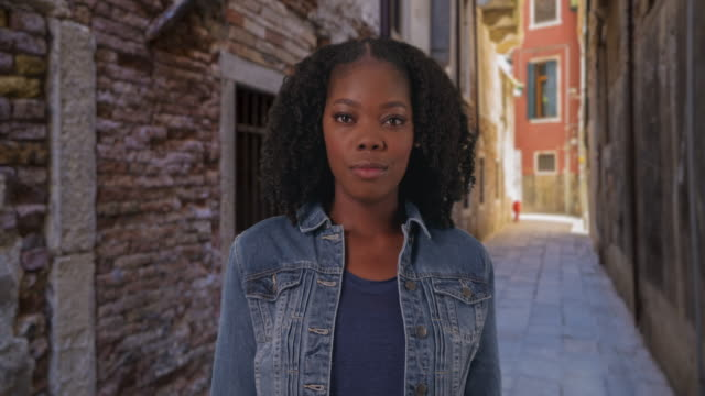 vídeos de stock, filmes e b-roll de casual portrait of attractive black woman in backstreet of florence - jaqueta jeans