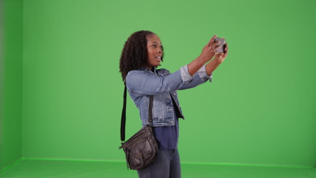 casual portrait of black female recording video with cellphone on green screen - {{asset.href}} stock videos & royalty-free footage