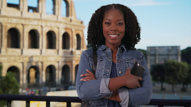 casual portrait of black female with radiant smile, roman coliseum in background - minnesmärke bildbanksvideor och videomaterial från bakom kulisserna