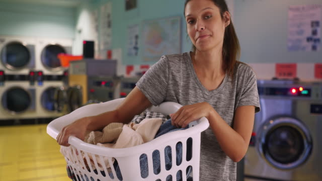 casual portrait of brunette girl holding basket of clothes in laundry room - tvättmedel bildbanksvideor och videomaterial från bakom kulisserna