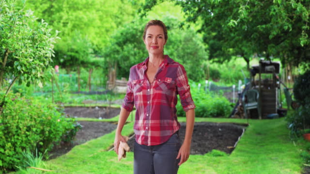 casual portrait of female farmer or gardener smiling with pride - gardening glove stock videos & royalty-free footage