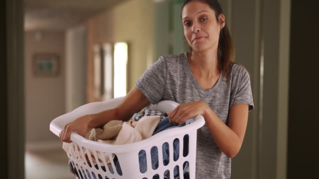 casual portrait of happy young woman at home holding basket of clean clothes - tvättmedel bildbanksvideor och videomaterial från bakom kulisserna