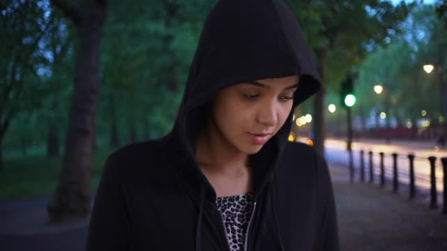 casual portrait of pretty latin female in hoodie sweatshirt at the park - sweatshirt stock videos & royalty-free footage