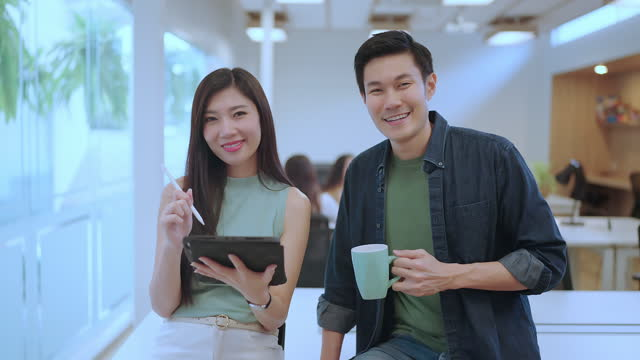 casual relax portrait of asian male and female confident startup team standing and smile together in office - business casual stock videos & royalty-free footage