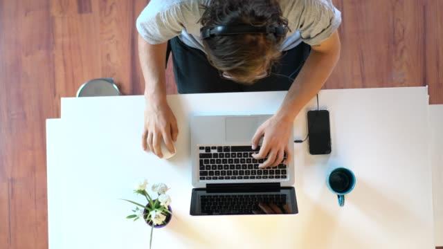 lässiger junger geschäftsmann sitzt am schreibtisch und hört musik mit kopfhörern - kreativer beruf stock-videos und b-roll-filmmaterial