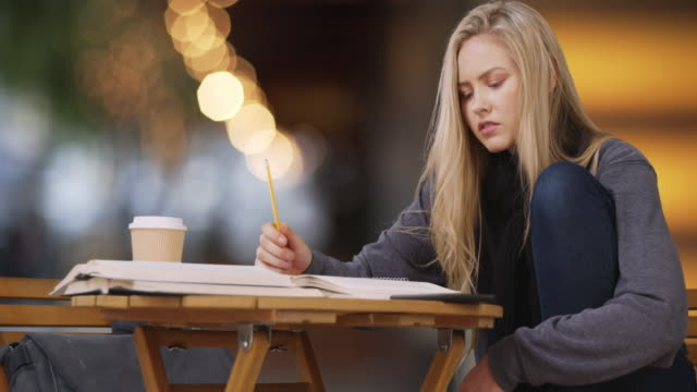 casual young female student sitting at table writing book report - broken pencil stock videos & royalty-free footage