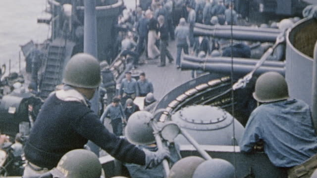 casualties being transferred from lsm to uss nevada alongside sailors working on deck and carrying stretchers some casualties completely covered with... - battle of iwo jima stock videos and b-roll footage