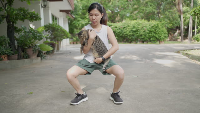 cat squat : woman does squats holding cat instead of gym weights at home exercise in lockdown covid-19 or corona virus - front view stock videos & royalty-free footage