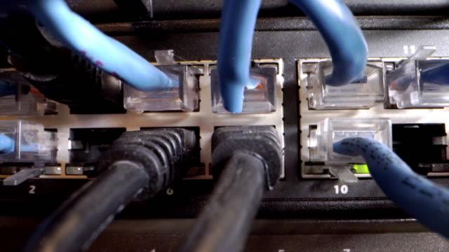 vidéos et rushes de cat5e ethernet câbles branchés dans un commutateur de réseau clignotant avec tangled messy high speed internet gigabit cat5 data patch cables en arrière-plan dans un placard de réseau informatique - câble
