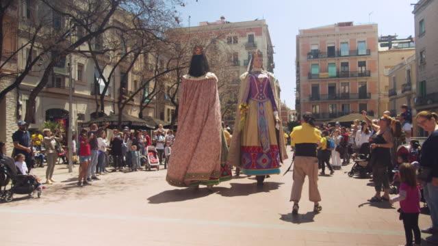 vídeos de stock e filmes b-roll de catalonia traditional celebration with gegants giant puppets at a barcelona gracia district square - fantoche