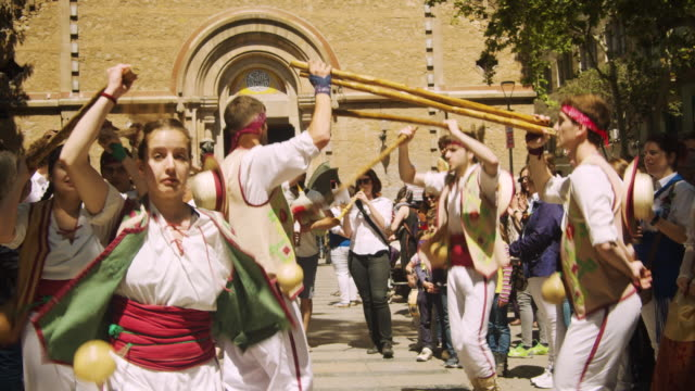 vídeos de stock e filmes b-roll de catalonia traditional dancing at barcelona. young group of people using with poles at gracia district square festival - pátio