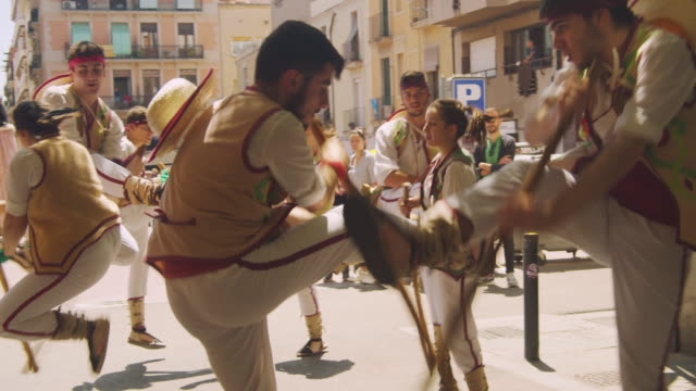 catalonia traditional dancing performance group of young people. jumping and hitting each other poles in a gracia district street of barcelona - spanien stock-videos und b-roll-filmmaterial