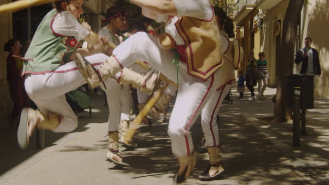 vídeos y material grabado en eventos de stock de catalonia traditional dancing performance group of young people. jumping and hitting each other poles in a gracia district street of barcelona - aldea