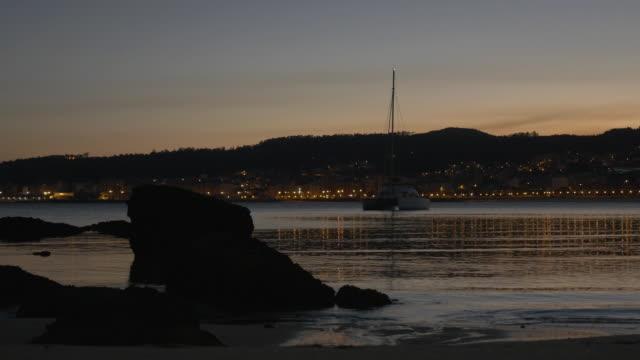 catamaran at dusk in calm waters bay - moored stock videos & royalty-free footage