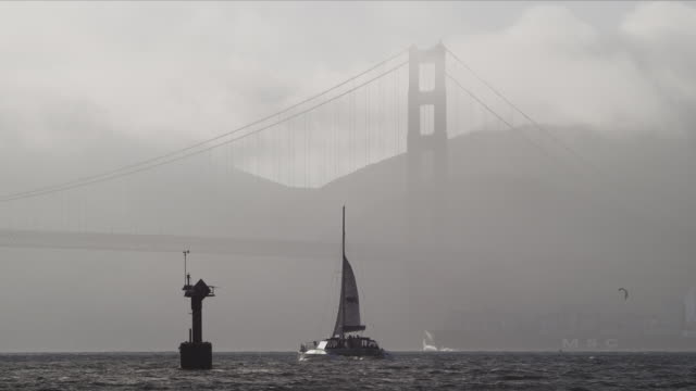 Catamaran sailboat comes about on San Francisco Bay, Golden Gate Bridge north tower in background, fog rolls in