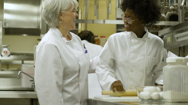 catering student learning how to roll pastry, teacher reassuring her. - rolling pin stock videos & royalty-free footage