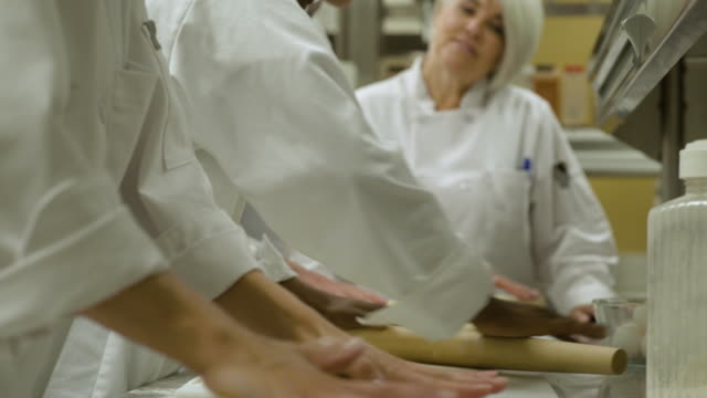 Catering students learning how to roll pastry, teacher explaining.
