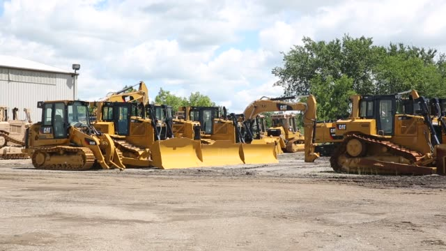 Caterpillar construction equipment sits in rows in a lot at the Altorfer Cat dealership in East Peoria Illinois on July 21 2015 Shots Wide shots pan...