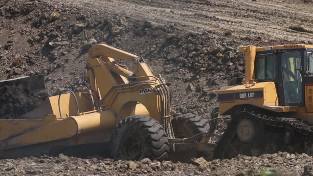 caterpillar construction vehicle excavates soil at a construction site 1080p generic construction - construction vehicle stock videos & royalty-free footage
