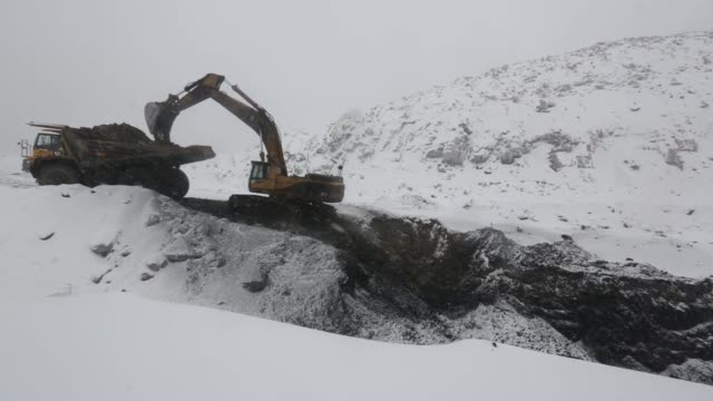 a caterpillar inc 375 hydraulic excavator loads coal onto a belaz oao dump truck at the raspadsky open pit mine operated by evraz plc in... - caterpillar inc video stock e b–roll